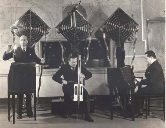 "'The Theremin Electro Ensemble' later called 'The Electrio' in 1932. (Left)Playing the RCA theremin is Leon Theremin's assistant, Julius Goldberg (with customised ""lightning bolt"" art deco, brass nickel chrome antennas). (Centre) playing the ""Theremin Cello"" is the Leonid Bolotine and (Right) Pianist Gleb Yellin is playing a Theremin Keyboard. In 1932, the ensemble could be heard on the radio every Monday afternoon at 2:15 over the Columbia Network, KMBC. (2)"
