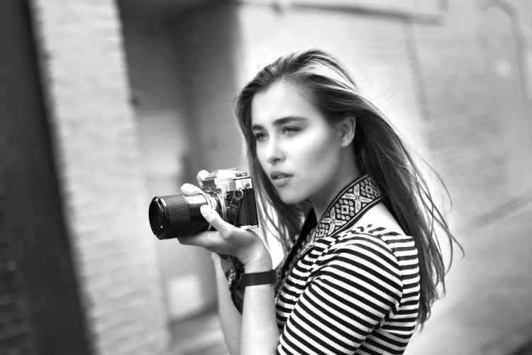 grayscale photo of woman holding a dslr camera