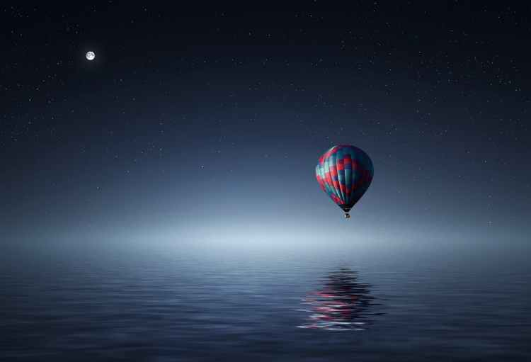 red and blue hot air balloon floating on air on body of water during night time