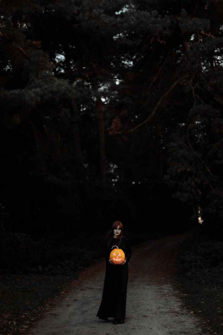 witch standing on a road with a pumpkin in her hands