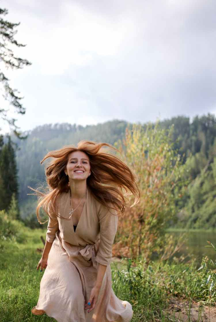 happy woman with flying hair on river coast