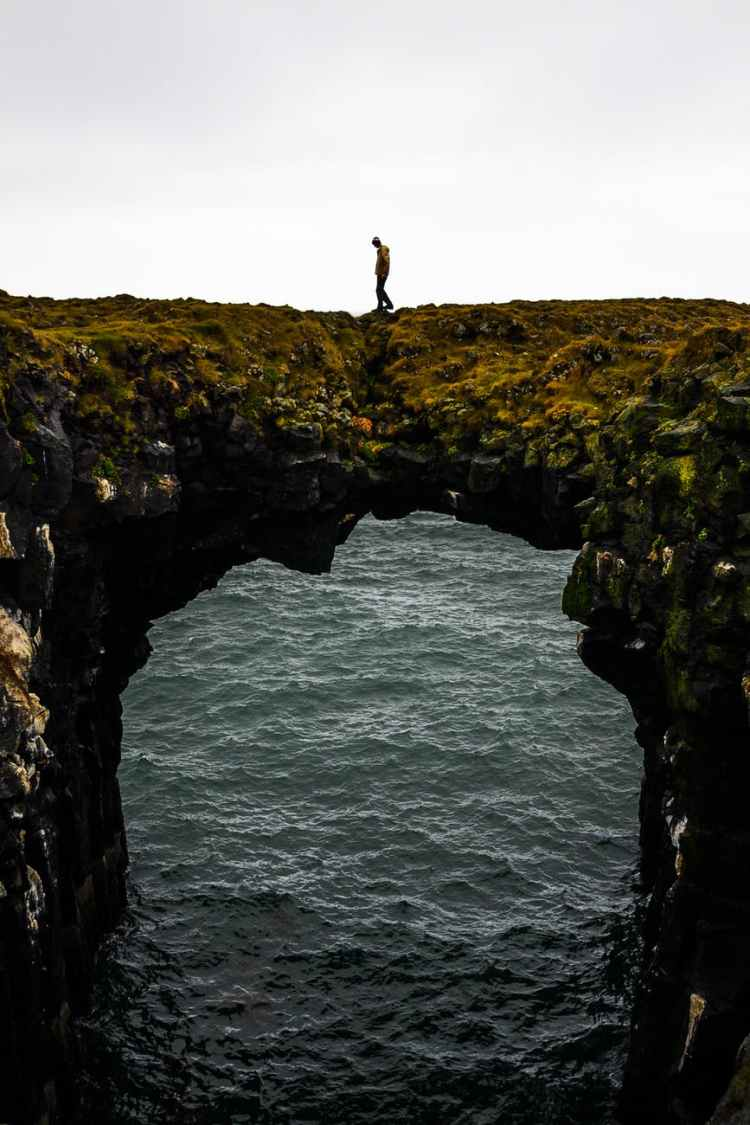 photography of a person standing on cliff