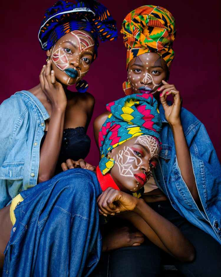 three woman with face paintings