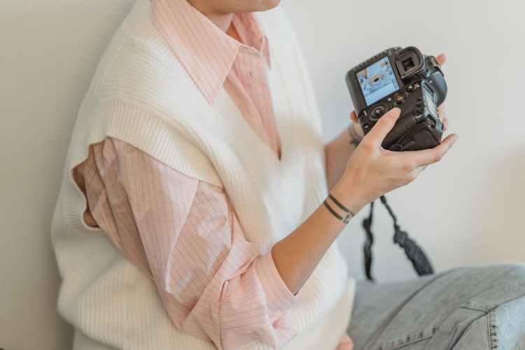 crop unrecognizable woman looking at photos in camera
