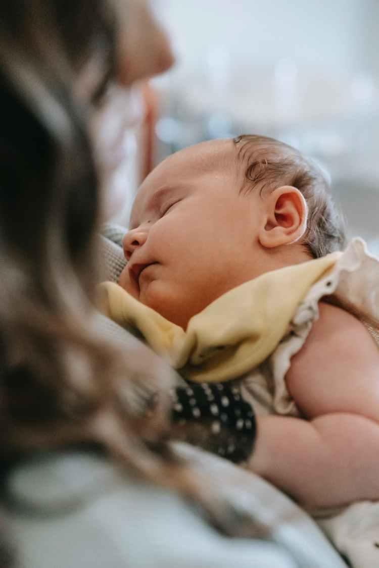 cute baby sleeping in hands of crop mother