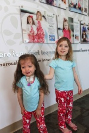 Tailyn and Bekah in front of their photo on the NICU Wall of Hope, which honors NICU grads.