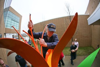 Artist Stephen Canneto arranges  the Daylily sculpture at the Akron Urban League