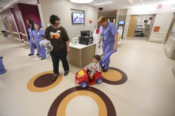 Child life specialist Alisa Mills lets Declan cruise around the pre-op unit with his mom, Erica, by his side.