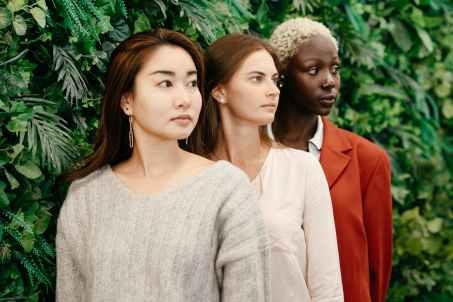 multiethnic confident businesswomen at green fence