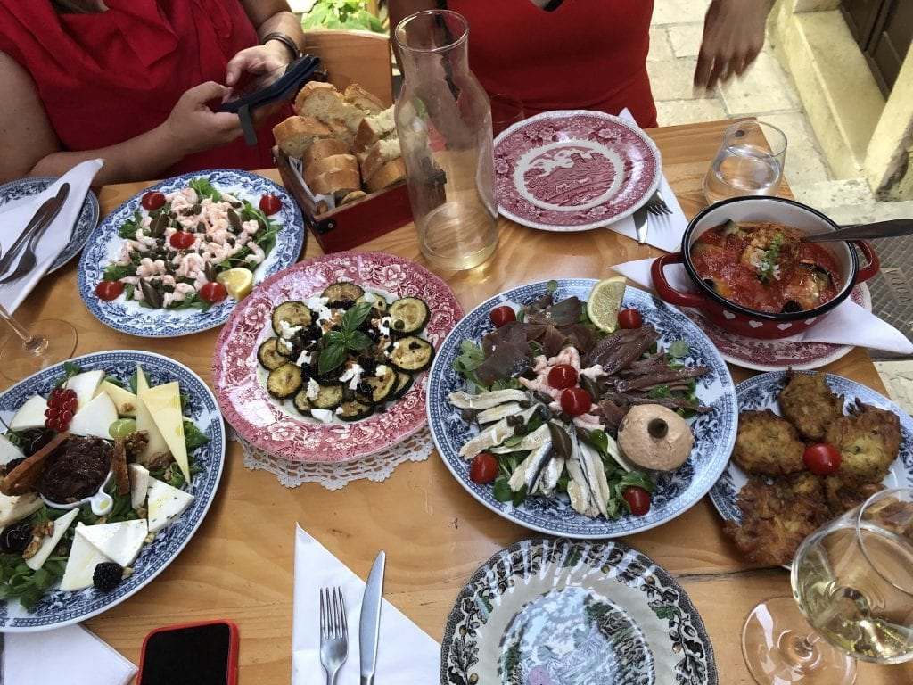 Small plates filled with lots of different apps along with wine glasses on a table in Korcula.