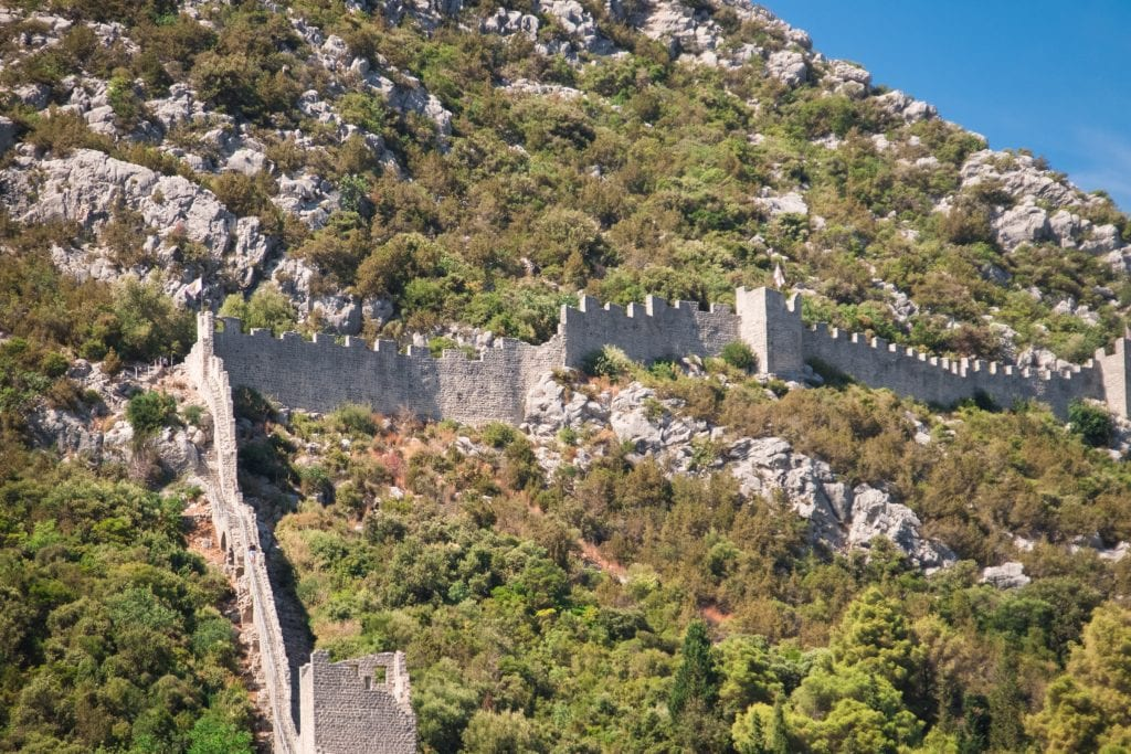 The Ston walls: A gray stone medieval wall running through the green mountains.