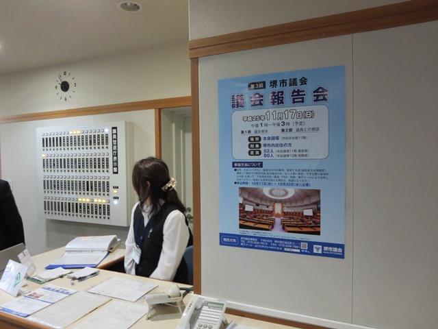 議会棟の受付。報告会のポスターが掲示されています