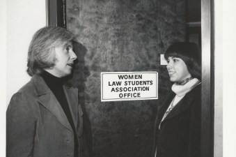 Two women stand outside the Women Law Student Association's office.