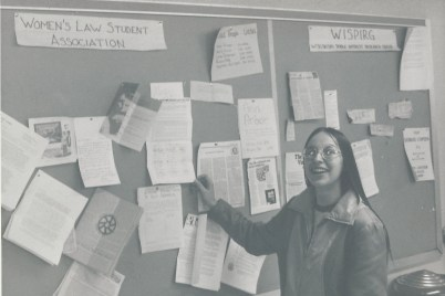 A student shows off the Women's Law Student Association bulletin board at the Law School.
