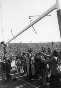 Student climbs goal post during the Cane Toss.