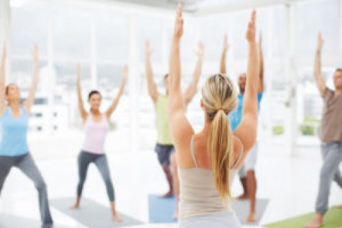 A young yoga instructor leading her class in some stretching exercises