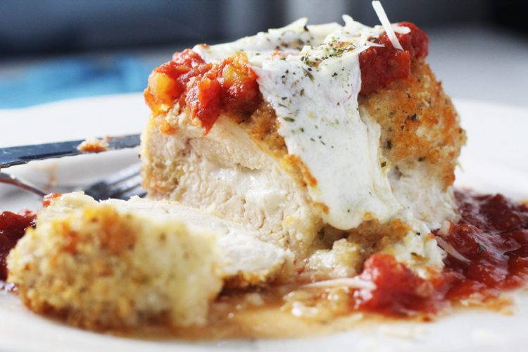 A white plate with breaded chicken stuffed with cheese, topped with sauce and melted mozzarella