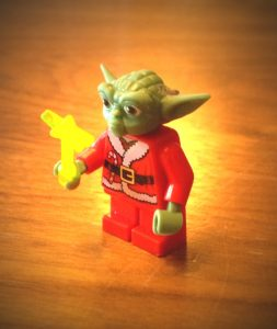 Yoda in a Santa's costume, carrying a magic wand