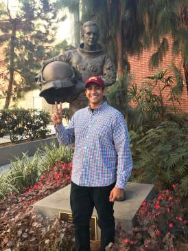 U.S. Navy Petty Officer, Second Class Kevin Moran standing in front of a statue of Neil Armstrong at USC's campus. He is displaying the fight on hand gesture.
