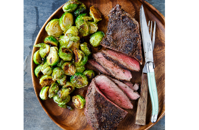Photo of a steak dinner with roasted brussel sprouts on the side.