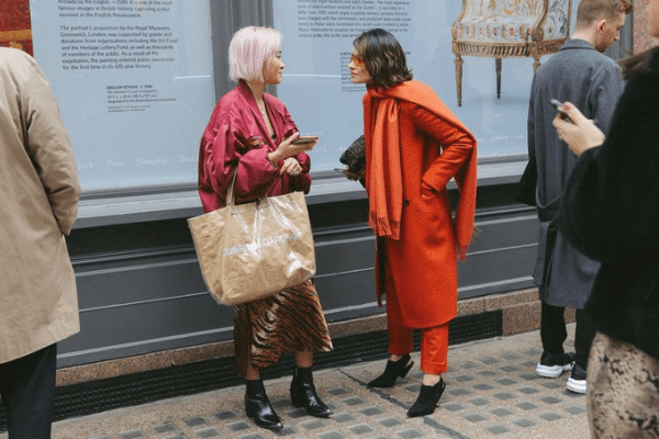 Woman wearing mauve bomber jacket and another woman wearing an orange coat.