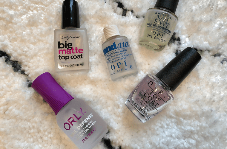 photo of manicure products such as base coat and top coat on white carpet