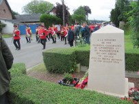 A pipe band troop past with some French veterans and local dignitories.