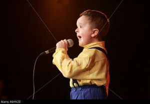 Singer kid boy 5 6 7 8 years old singing on a stage performance performing communicating microphone mike concert rehearsal feeli