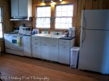 Cozy kitchen with refrigerator, stove, oven, coffee maker, toaster, and microwave