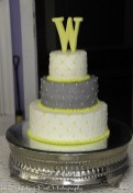 Yellow and gray weddng ake topped with W