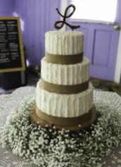 Burlap ribbon wedding cake with base of babies breath