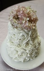 Icing roses on wedding cake topped with pink silk hydrangea