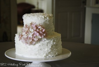 White rough iced wedding cake with pink hydrangea