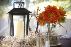 Centerpieces of lanterns, mums, submerged sticks, and spanish moss