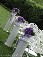 White columns topped with purple and lilac silk flowers