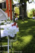 Hobnail glass jars hung from shepherd's hooks with red ribbon and white hydrangeas