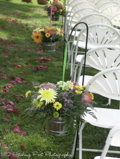 Live flowers in galvanized tin buckets with hung by colored ribbons