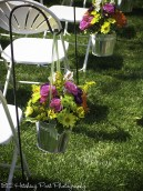 Pink, yellow, and lime flowers in galvanized buckets