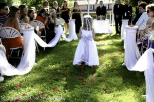 Columns used on the lawn topped with red petals.  White tulle completes the look
