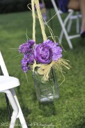 Silk purple flowers in raffia tied mason jar