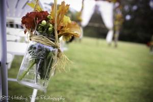 Silk flowers in mason jar hung with raffia