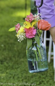 Coral, yellow, and pink flowers in blue mason jar