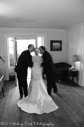 Bride gets kiss from dads