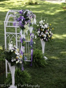Lilac and white silk flowers on arbor with florist arrangements and ferns on ground