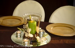 Green candle with magnolias set in coffee