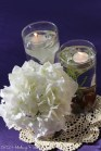 Floating candles, rocks, and silk flower centerpiece
