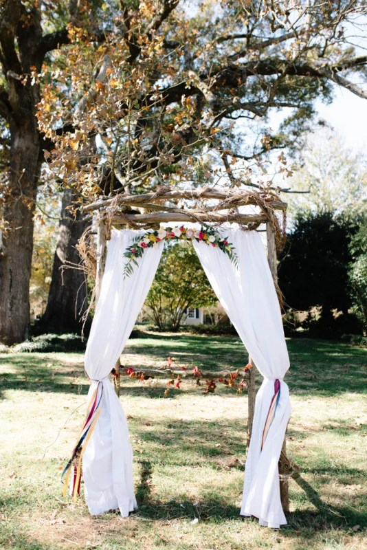 Solid white drapes tied with bride provided ribbon and felt flowers