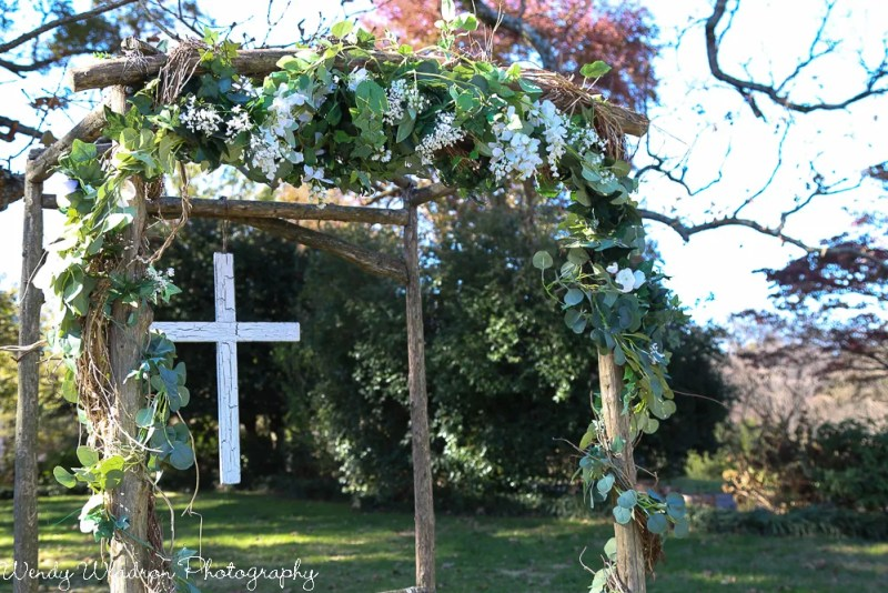 Wood arbor with silk greenery, small scale white flowers, and wooden cross