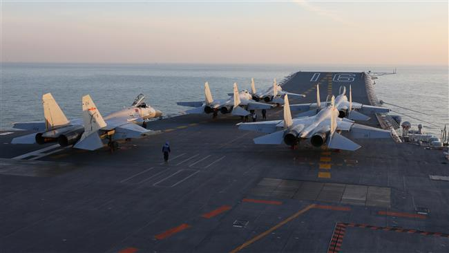 This file photo, taken in December 2016, shows Chinese J-15 fighter jets waiting on the deck of China's Liaoning aircraft carrier during military drills in the Bohai Sea, off China's northeast coast. (By AFP)