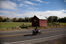 2013-July-August-Oregon-Travel-Explore-Eastern-Oregon-Tim-Labarge-Riding-by-Barn-Motorcycle